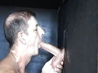 Deep sucking of big cock through gloryhole