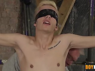 Blindfolded and strapped twink gets a handjob and blowjob