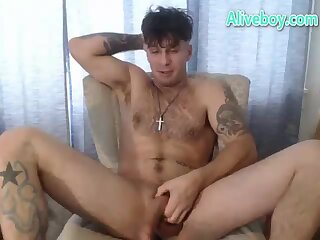tattooed handsome hunk tugging his big cock